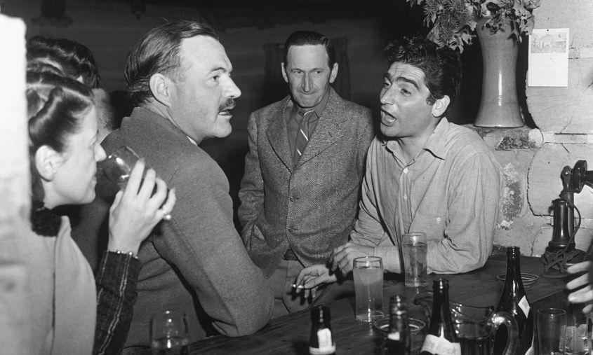 Hemingway drinking in a bar, talking to photojournalist Robert Capa in 1940