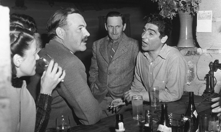Hemingway drinking in a bar, talking to photojournalist Robert Capa in 1940